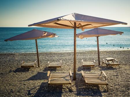 Photo pour Sun umbrellas and wooden beach beds on the sea pebble beach - image libre de droit