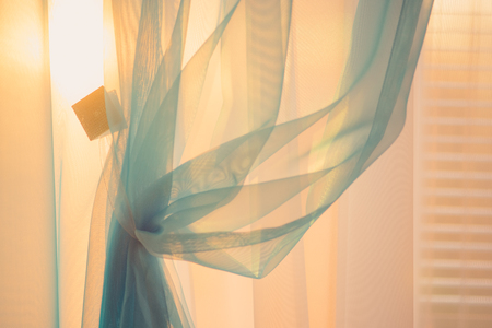 Photo pour Sun at sunset light through the thin curtains on the window with blinds - image libre de droit