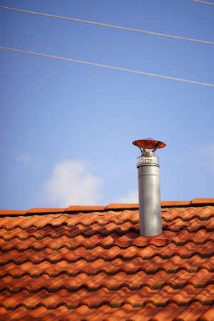 Photo pour Red tile roof with galvanized chimney chimney against blue sky. - image libre de droit