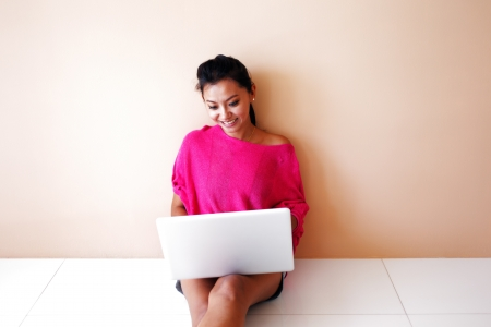 Young woman in a pink top using a laptop and smiling