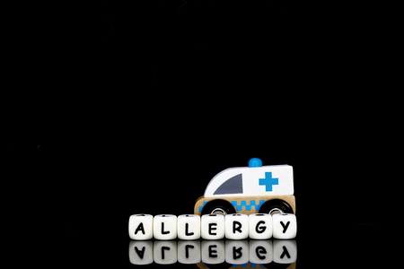 Alphabet letters spelling the word  allergy with a model ambulance in the background.  A concept of medical condition which requires urgent medical attention.