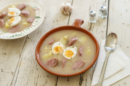 Traditional polish soup called Zurek with eggs and sausage on wooden background