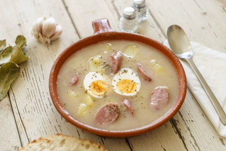 Traditional polish soup called Zurek with eggs and sausage surrounded by spices