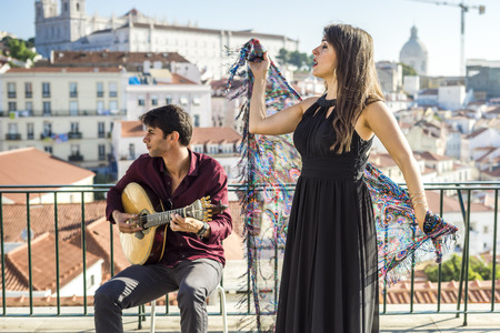 Beautiful fado singer performing with handsome portuguese guitarist player in Alfama, Lisbon, Portugal