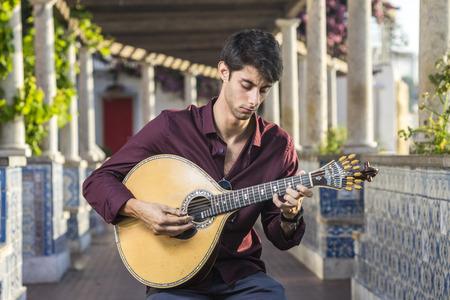 Fado musician playing on portuguese guitar under pergola in Alfama, Lisbon, Portugal