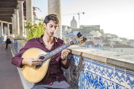 Fado musician playing on unique portuguese guitar in Alfama, Lisbon, Portugal