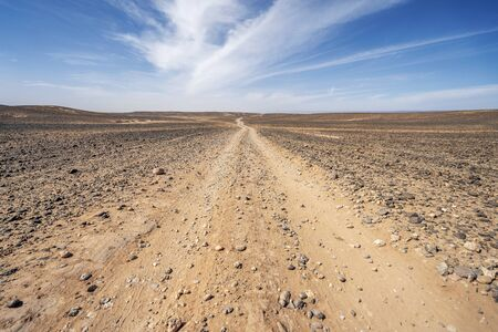 Photo for Dirt, long road through endless Sahara desert, Morocco, Africa - Royalty Free Image