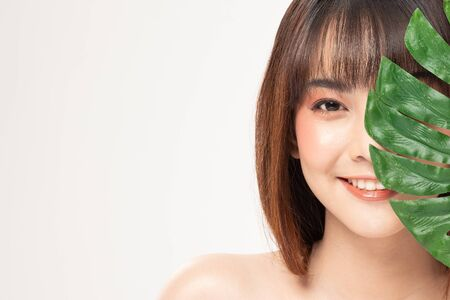Foto de Beauty asian woman  brown hair looking smile in camera happiness and holds a large green tropical leaf in hands and covers a part of her face and cheerful with make up brush,Beauty Concept on white background. - Imagen libre de derechos