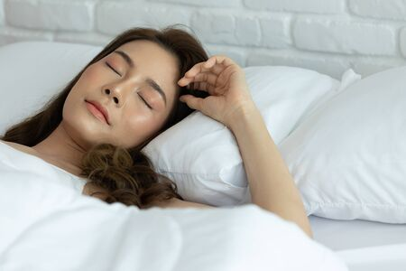 Photo pour Beautiful woman sleeping on white bed in the bedroom,sweet dreams, keeps eyes closed, enjoys good rest at home and calm atmosphere. People and rest concept. - image libre de droit