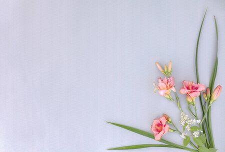 Photo pour Corner frame with flowers of lilies on grey paper - image libre de droit