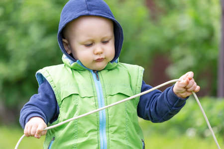Photo pour A toddler dressed in a vest and hoodie with an electric wire in his hands plays an electrician in nature - image libre de droit
