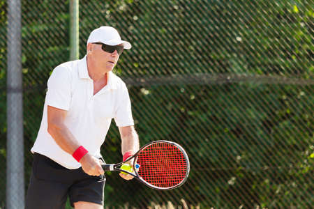 Photo for Close-up of an elderly tennis player playing tennis on an outdoor court - Royalty Free Image