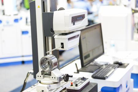 operator inspection automotive part by contour measuring machine