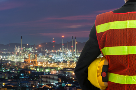 Photo pour Hand or arm of engineer hold yellow plastic helmet in front of oil refinery industry - image libre de droit