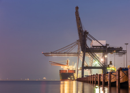 Foto de Containers loading by crane on morning dark, Trade Port , Shipping , transport - Imagen libre de derechos