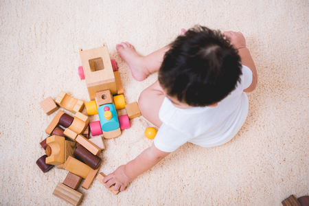 Photo pour Top view asian child building playing toy blocks wood indoors room - image libre de droit
