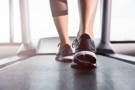Foto de Feet of woman exercise workout running on treadmill at fitness gym - Imagen libre de derechos