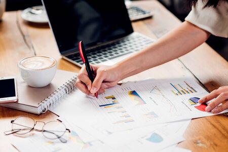 Foto de Lifestyle freelance woman and laptop computer he examined the graph profit docume in coffee shop - Imagen libre de derechos