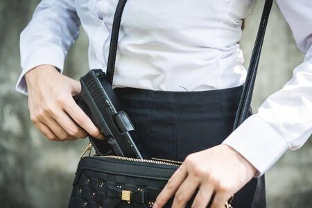 Photo pour Young woman with concealed weapon gun in her small handbag - image libre de droit