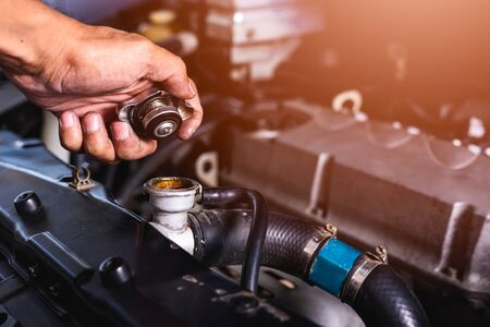 Photo for Hand of auto mechanic technician service check cooling water he open radiator cap the in garage - Royalty Free Image