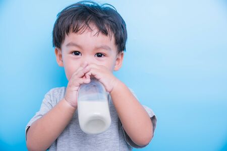 Photo pour Asian little child boy about 2 year drinking milk from bottle glass itself on blue background - image libre de droit