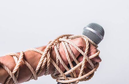 Photo pour Hand holding microphone and have roped on fist hand on white background, Human rights day concept - image libre de droit