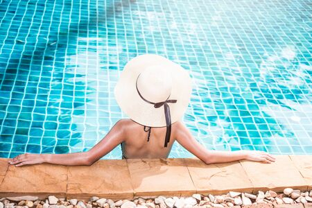 Photo for Back young woman and hat luxury on vacation summer swimming pool at resort - Royalty Free Image