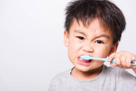 Photo pour Closeup Asian face, Little children boy hand holds toothbrush he brushing teeth myself on white background with copy space, health medical care - image libre de droit