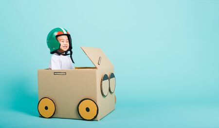Photo for Happy Asian children boy with Helmet smile in driving play car creative by a cardboard box imagination, summer holiday travel concept, studio shot on blue background with copy space for text - Royalty Free Image