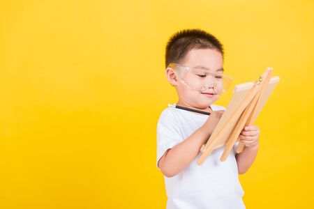 Photo pour Asian Thai happy portrait cute little cheerful child boy smile are drawing on blackboard and looking the board, studio shot isolated on yellow background with copy space - image libre de droit