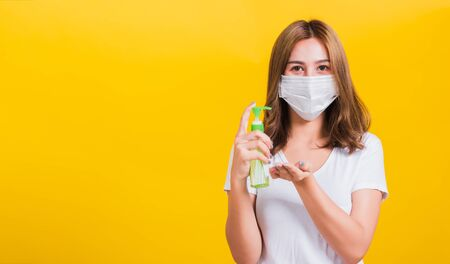 Photo pour Portrait Asian Thai beautiful young woman wear mask protection clean corona virus on hand with alcohol gel or antibacterial soap sanitizer, studio shot isolated on yellow background, with copy space - image libre de droit