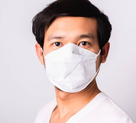 Photo pour Closeup Asian handsome Man wearing surgical hygienic protective cloth face mask against coronavirus, studio shot isolated white background, COVID-19 medical concept - image libre de droit