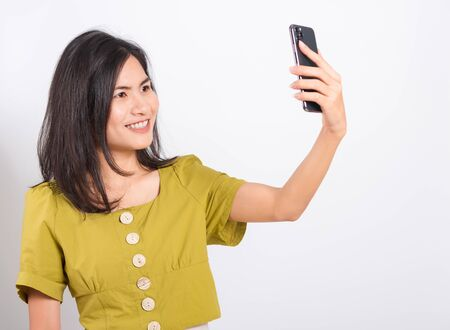 Photo pour Portrait Asian beautiful happy young woman standing smile, holding mobile phone her taking selfie on white background, with copy space - image libre de droit