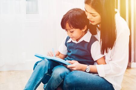 Photo pour Happy Asian child kid boy son kindergarten and young beautiful parent mother teaching drawing and play color together at interior room home, family day and Back to school concept - image libre de droit