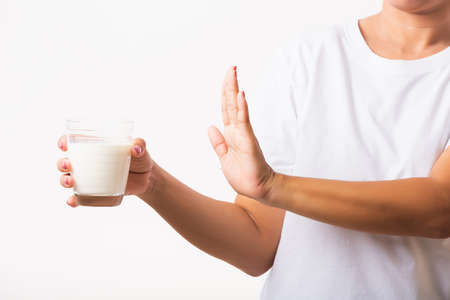 Photo pour Closeup woman raises a hand to stop sign use hand holding glass milk she is bad stomach ache has bad lactose intolerance unhealthy problem with dairy food, studio shot isolated on white background - image libre de droit