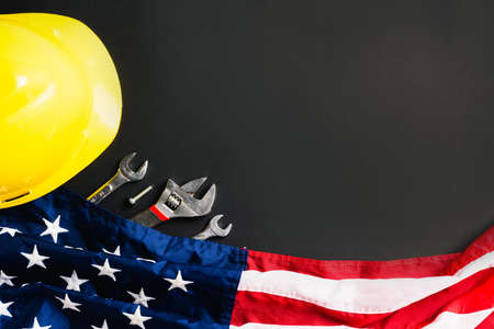 Foto de Labor day concept, Top view flat lay of different kinds wrenches with American flag on black. First Monday in September, creation of labor movement and dedicated to social of the American worker - Imagen libre de derechos