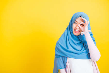 Photo pour Asian Muslim Arab, Portrait of happy beautiful young woman Islam religious wear veil hijab funny smile she show gesture fingers in okay gesture symbol, OK sign over her eyes isolated yellow background - image libre de droit