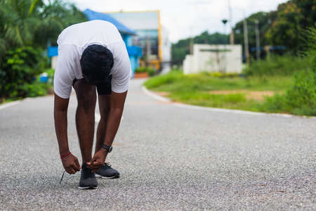 Foto de Close up Asian sport runner black man standing he trying shoelace running shoes getting ready for jogging and run at the outdoor street health park, healthy exercise workout concept - Imagen libre de derechos