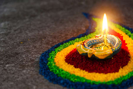Photo for Close up clay lit light a fire already on Diya or oil lamp on concrete background, Decoration of Hinduism rangoli, Happy celebration Deepavali, or Diwali Indian festival concept - Royalty Free Image