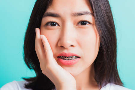 Photo pour Portrait of Asian teen beautiful young woman smile have dental braces on teeth laughing she unhappy pain toothache and touch cheek by hand, isolated on blue background, Medicine and dentistry concept - image libre de droit