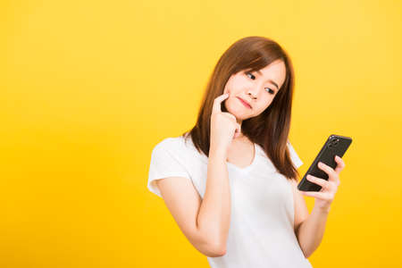 Photo pour Asian happy portrait beautiful cute young woman teen standing wear t-shirt her using holding smart mobile phone and thinking looking to the phone isolated, studio shot yellow background with copy space - image libre de droit