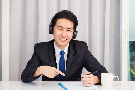 Photo pour Work from home, Asian young businessman wear suit video conference call or facetime he smiling sitting on desk wearing headphones and raise his hand point finger to a paper job he looking to camera - image libre de droit