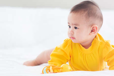 Photo pour Portrait of beautiful young Asian newborn little baby prone on the bed at home, Happy baby smile wears a yellow shirt relaxing in the room, Family morning at home - image libre de droit