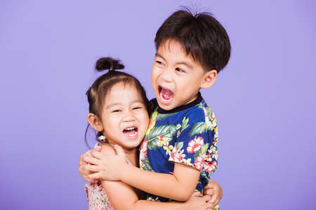 Photo pour Asian Two happy funny little cute kids stand together in studio shot isolated on purple background, happy family brother and sister hugging each other feeling love (4 years old boy, 2 years old girl) - image libre de droit