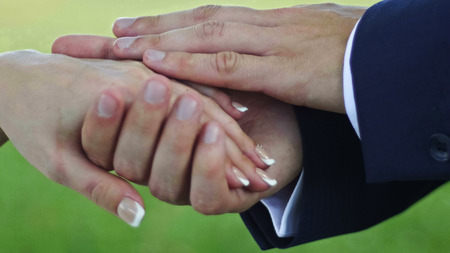 Hands of groom and bride, outdoor - in the meadow, close up