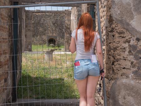 Foto de Attractive red hair woman looking to museum in pompeii, Italy - hot summer midday - Imagen libre de derechos