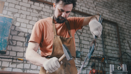Blacksmith with hammer in forge creating steel knife: Royalty-free
