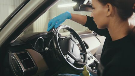 Car cleaning - attractive young woman is washing interior of a luxury vehicle with a brush