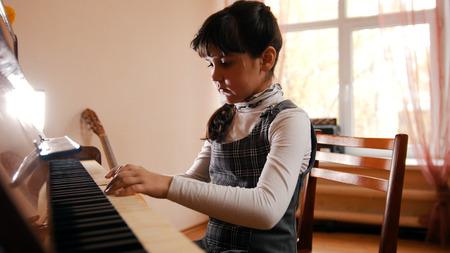 Foto de A little girl playing piano on music lesson. Beautiful sunlight. Hands on keys - Imagen libre de derechos