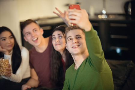 Young friends sitting on the sofa and young man taking a selfie
